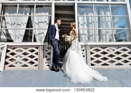 Wedding couple on the nature is hugging each other. Beautiful model girl in white dress. Man in suit. Beauty bride with groom. Female and male portrait. Woman with lace veil. Lady and guy outdoors
