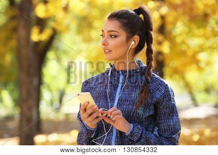 Young beautiful woman holding phone, listening to music with headphones in the autumn park