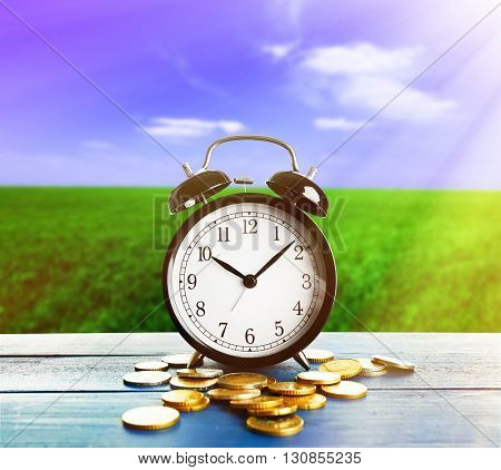 Alarm clock and money coins on wooden table