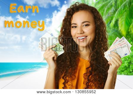 Beautiful young girl holding cash on resort background