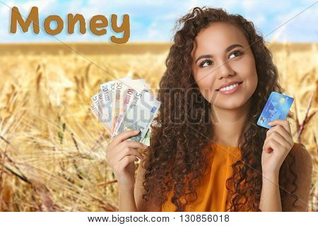Beautiful young girl holding cash and credit card on blurred natural background