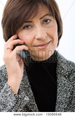Closeup portrait of senior businesswoman talking on mobile phone. Isolated on white background.