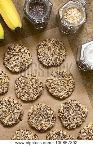 Vegan cookies made of banana oatmeal and roasted oat grains linseed poppy seeds grated coconut chia seeds and cinnamon powder photographed overhead with natural light (Selective Focus Focus on the top of the cookies)