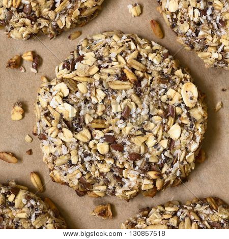 Vegan cookie made of banana oatmeal and roasted oat grains linseed poppy seeds grated coconut chia seeds and cinnamon powder photographed overhead with natural light
