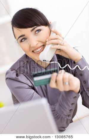 Smiling young women shopping online at home, holding credit card in hand and talking on phone.