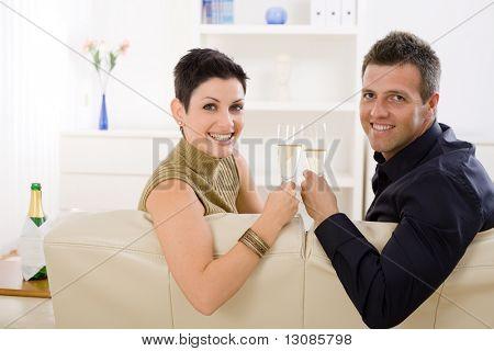 Feliz pareja tintineo champagne gafas en casa en el sofá. Sonriendo y mirando a cámara.