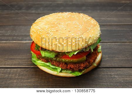 Classic american burger fast food. Big double burger at wood. Hamburger with fresh vegetables and meat. Burger with cheese, beef, tomato, lettuce. Cheeseburger at rustic wooden background.
