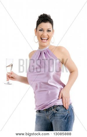 Happy young woman dressed for party holding a glass of champagne, laughing. Isolated on white background.