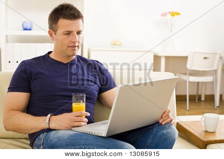 Man sitting on sofa at home and using laptop computer.