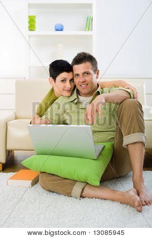 Casal jovem browing internet em casa no computador portátil, sentado no chão e deitado no sofá, embra