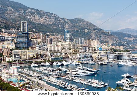 Monte Carlo harbor with luxury yachts and the city skyline in the background
