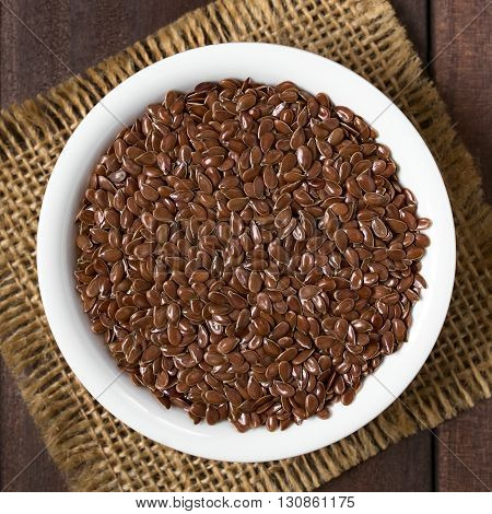 Brown flax seeds or linseeds in small bowl photographed overhead with natural light (Selective Focus Focus on the top of the seeds)