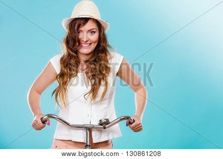 Active happy woman riding bike bicycle. Young girl in hat white shirt and shorts. Healthy lifestyle and recreation leisure activity. Studio shot.