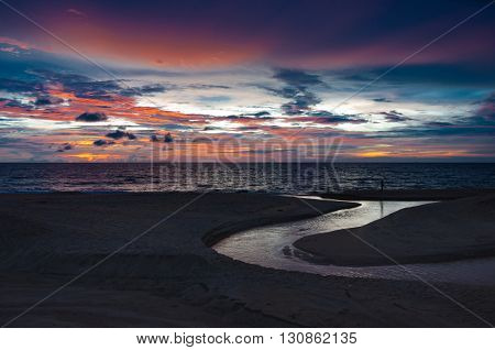 Romantic twilight sky in the evening with small canal on the beach