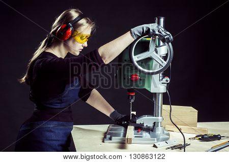 beautiful female carpenter at work using vertical drilling machine. Photo on black background.
