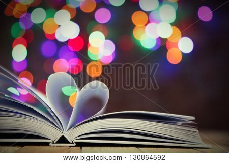 Sheets of book curved into heart shape on wooden table against unfocused lights