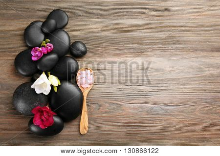 Beautiful spa composition with stones and freesia on wooden background