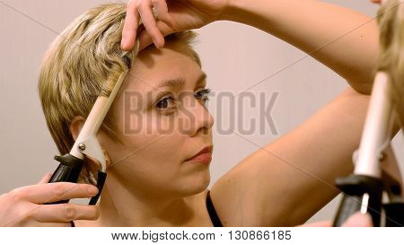Pretty blond short hair woman curls her hair with curling iron in front of mirror. Beauty and makeup concept.