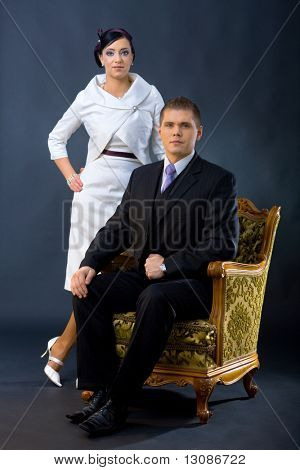 Portrait of young couple dressed in elegant clothes. Man wearing three-pieces dark suit, sitting in armchair. Woman wearing white cocktail shirt with jacket, standing beside him.