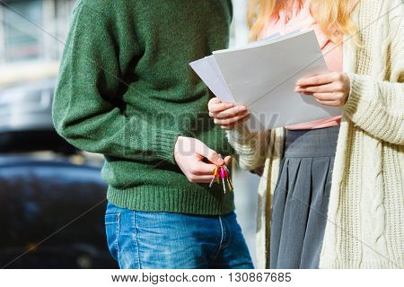Relationship family finances house problem debt concept. Couple standing holding paper keys. Man with woman holding documents and colorful keyring.