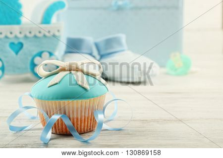 Tasty cupcakes with bow and baby shoes, decorative baby carriage and photo album  on color background
