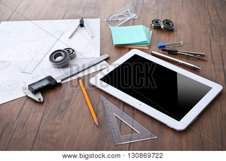 Tablet and engineering tools on wooden background