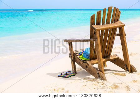 Wooden beach chair with hat and slippers at beach cost summer holiday concept