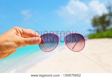 Hand holding Pink Sunglasses on beautiful lonely beach