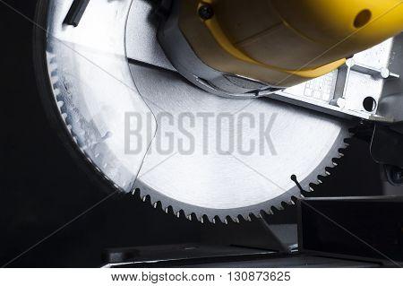 miter saw. Cutting disk on black background.