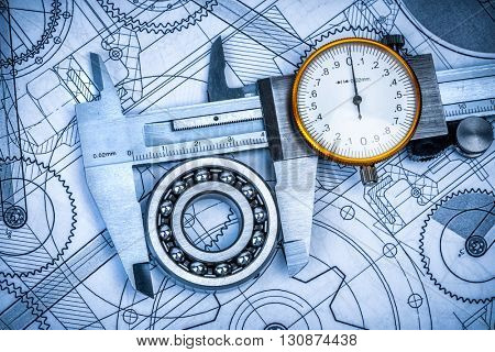 Metal vernier caliper and Ball bearings on technical drawing a blue toning