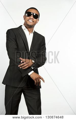 A young happy black male wearing sunglasses, white button down shirt with a custom suit jacket being playful in a studio setting on a white background.
