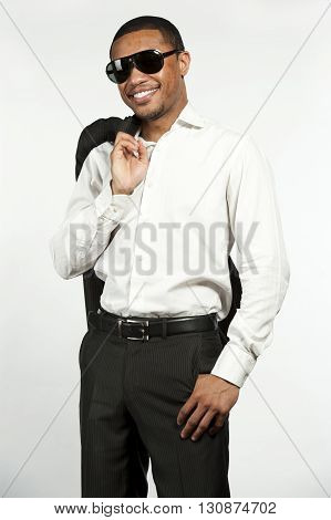 A happy young chic black male wearing sunglasses, white button down shirt with black pants with sports jacket over his shoulder in a studio setting on a white background.