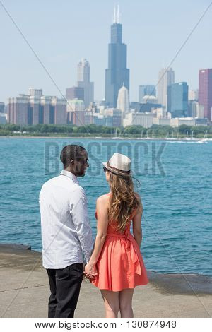Adorable and romatic couple spending their time by the riverside on a sunny morning. On the background, high rise buildings and the blue sky is also seen.