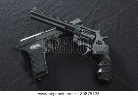 semiautomatic pistol and revolver on black background.