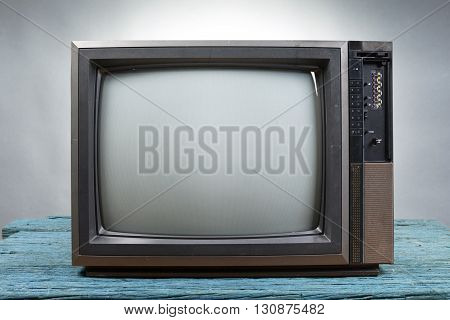 Vintage Television on wood table on gray background