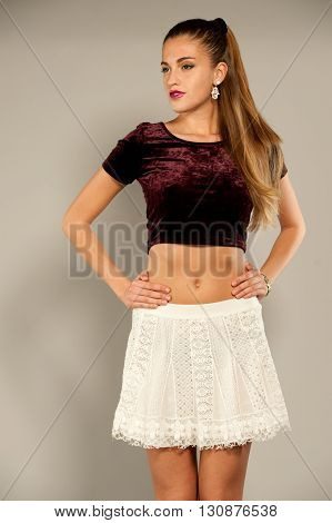 Brunette caucasian model with wavy hair wearing a maroon top and a white short skirt on a grey background in a photo shoot. She is seen from her knees up in a casual pose.