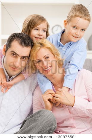 Portrait of happy family, children embracing their parents from behind.