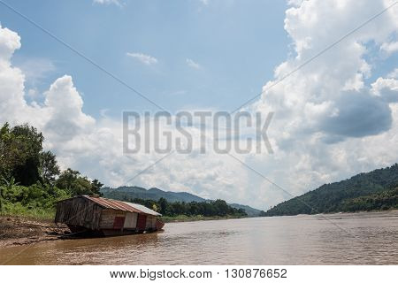 View of a hill and boat from the Mekong river in Laos. Mekong is the largest trans-boundary Southeast Asian river in Laos. The river is surrounded by hills that looks amazing.