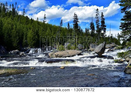 the rapids flow over rocks in the gibbon river