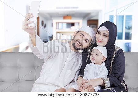 Two Arabic parents and their son sitting on the sofa while taking selfie picture together at home