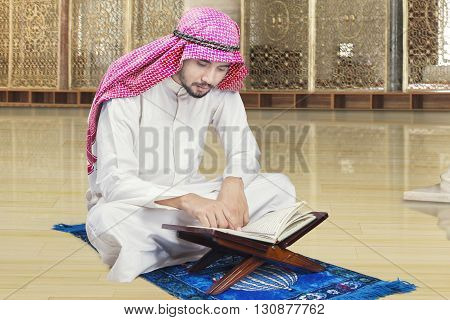 Portrait of Arabic person sitting in the mosque while reading Quran and wearing traditional clothes