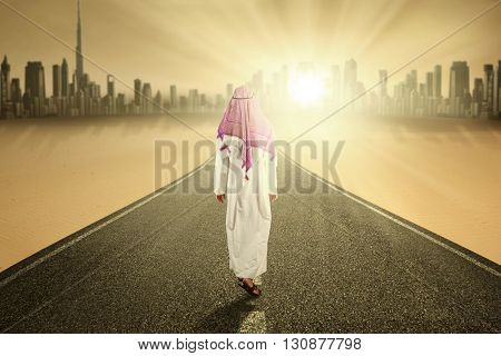 Image of Arabic person wearing traditional clothes and walking forward on the road