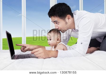 Portrait of curious baby boy watching the laptop screen with his father in the bedroom