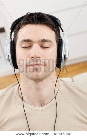 Casual man listening music with headphones at home, relaxing with closed eyes.