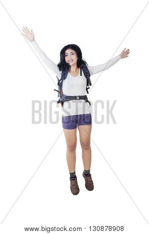 Portrait of a joyful female hiker jumping in the studio while carrying a backpack isolated on white background