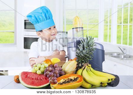 Portrait of a little boy wearing a cooking hat while making fruits juice in the kitchen at home