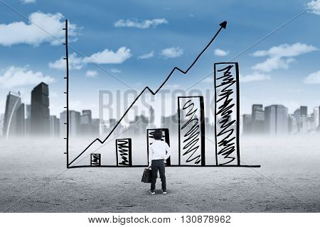 Picture of little businessman carrying bag and looking at a growing chart with upward arrow shot outdoors