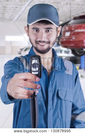 Portrait of Arabic mechanic giving a car key while smiling and wearing uniform in the workshop