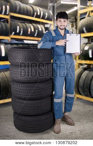 Portrait of middle eastern mechanic standing next to a pile of tires while showing empty clipboard in the workshop