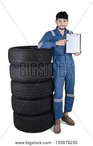 Middle eastern mechanic standing next to a pile of tires while showing empty clipboard isolated on white background